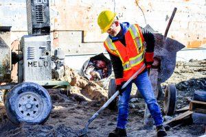 A construction worker shovels on a job site.